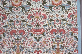 Symmetrical floral pattern on white ground. Field broken into ogival units by swinging rose-colored bands. Polychrome.