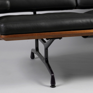 Cast aluminum frame with four legs, with open strut support system. Frame coated with epoxy paint. Base of walnut with webbed support. Struts continue from legs up back of sofa to support two shaped walnut horizontal elements. Seat and back upholstered in leather with rectangular paneled cushions. Two rectangular horizontal arms with similar cushions.