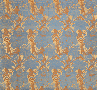 Textile with a light brown satin ground with a design in blue and darker brown of massive foliage with wide human figures and animals.