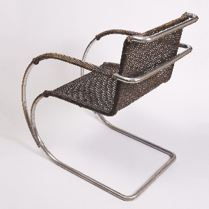Cantilevered chair with a curved support made of tubular steel, on which a cane seat and chair are woven tightly. The use of curved tubular steel and the cantilever design give the chair an airy and light look.