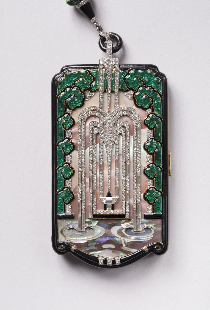 Rectangular Mauboussin compact whose central plane boasts a cascading fountain of diamonds spilling into a mother-of-pearl pool and surrounded by abstracted green enamel foliage. At bottom a stylized swag frames the scene while at top the scene terminates in a geometric finial attached to a diamond- and onyx-striped ring.