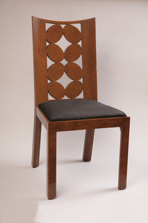 Bird's-eye maple dining chair with back of oval openwork and seat of black fabric upholstery.