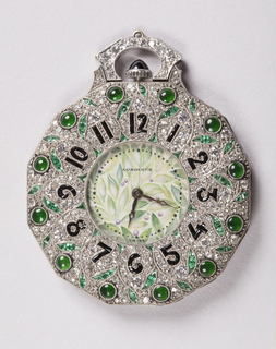 Twelve-sided pocket watch covered in pave diamonds and repeating stylized floral decoration articulated in platinum with cut and cabochon emeralds and numerals of cut black gems. At center, watch hands and Longines brand name rest against a leaf-and-berry pattern while the dial is protected by a waisted pavéd element at top.