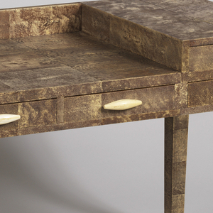 Rectangular writing desk on four tapering legs, square in section; the whole covered with brown-beige mottled shagreen (manta ray skin); six drawers with oblong ivory pulls.