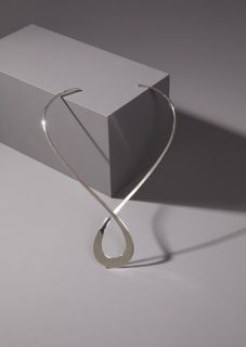 Rigid silver necklace looped in the center.