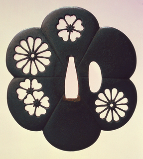 Iron tsuba (sword hilt) with scalloped edges and flower-shaped piercings.