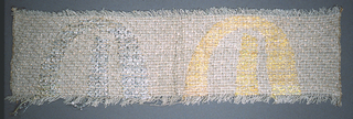 Handwoven sample with off-white warp and off-white and metallic gold weft. The Hebrew letter shin is brocaded on the left in shades of yellow and the right in shades of grey with metallic silver.