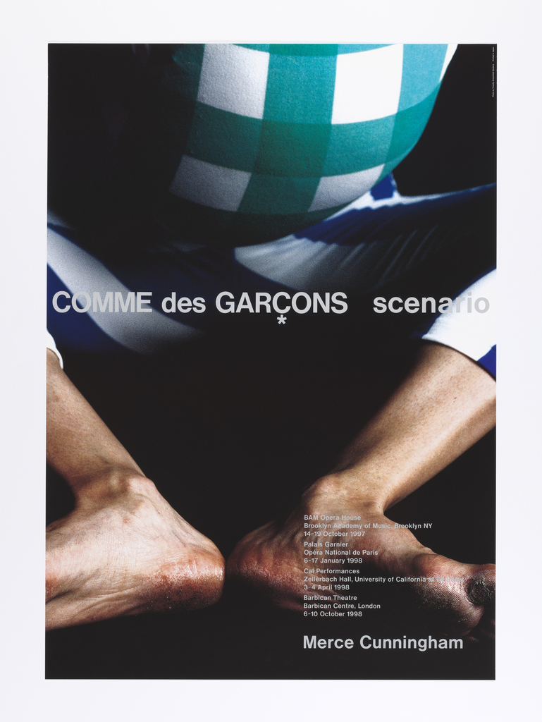 "Vertical format poster advertising dance performance of ""Scenario,"" choreographed by Merce Cunningham with costumes by Rei Kawakubo of Comme des Garçons. On black ground, a four-color photograph detail of a dancer's body, bare calloused feet at bottom center with toes pointed outwards. At top, details of the dancer's costume, including blue and white striped pants and a checkered green and white shirt, the upper body extremely round. Printed text in gray at center and at lower right."