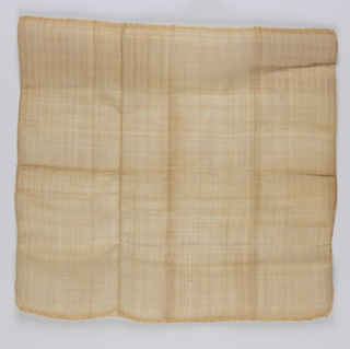 Square comprised of three fragments stitched together. Light tan pineapple fiber ground with a faint plaid of orange pineapple fiber and white cotton. Machine hemmed.