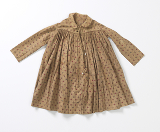 Very full skirt falling from shoulder yoke, round neck with Peter Pan collar, long sleeves, buttons down back. Entire dress made from a double thickness of fabric, which is strie brown and white with tiny bud repeat in red, green, brown and white.