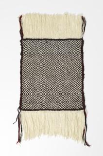 Interlocked twill fret pattern. Ivory warp and dark brown wool weft. Red cotton stripe in sides. 7 inch warp fringe at both ends.
