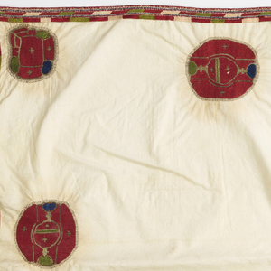 Firm white cotton cloth with large irregular medallions in dark rust with touches of blue and green; metallic thread around border. Narrow embroidered edge in same colors. Tassels on four corners.