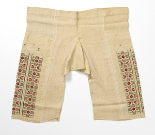 Coarse linen trousers, embroidered in panels down side of leg. Design is of stylized flower head, open, flat, worked in red cross stitch edged with pink, and at four points the glower heads in profile worked in gold thread. Panel outlined in green silk; panels separated by a band of drawn thread whipped over in white silk.