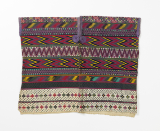 Design in purple, red, black, green, yellow and blue in extra wefts, almost completely concealing the white ground fabric. The predominant pattern is geometric, especially a zigzag motif in horizontal registers. Lower border has stylized floral forms brocaded and some elements of the design appear to have outlining that is embroidery.