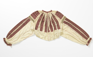 Short, full blouse of fine cream linen gathered to a stand-up neckband. Long, full sleeves are gathered at the wrist with a ruffle. Embroidery in red silk cross-stitch and gold thread wound on a linen core, and gold paillettes. Pattern of wide stripes radiating from the neck down the sleeves, with geometric inner decoration.