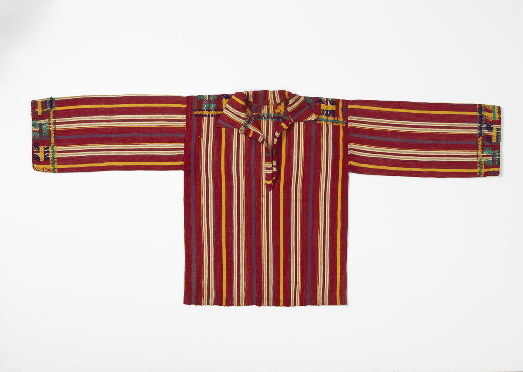 Red shirt with yellow, lavender, white, tan, and green stripes. Weft patterning on yoke and cuffs of stylized animals in green, yellow, purple and lavender.