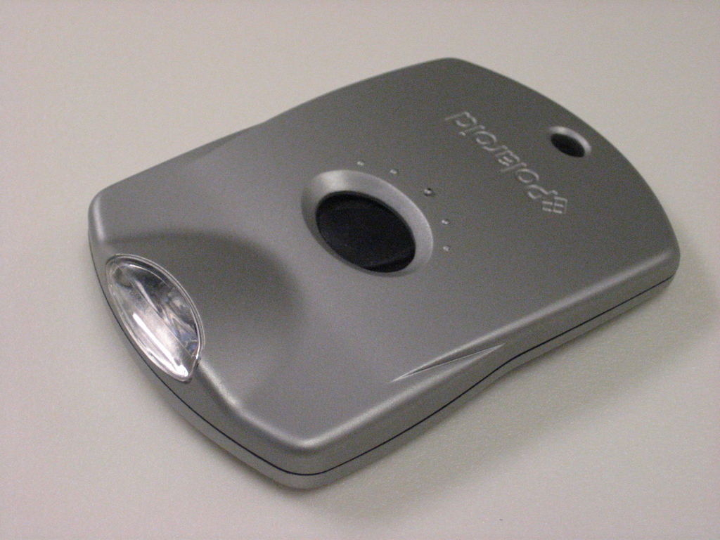 Contoured rectangular silver form, black oval switch near center.