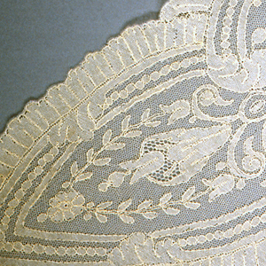 Triangular-shaped shawl of machine lace. In the center, the pattern shows a bunch of roses with two curved rose vines on either side. Slightly scalloped border of guilloche and lobes with flowers.