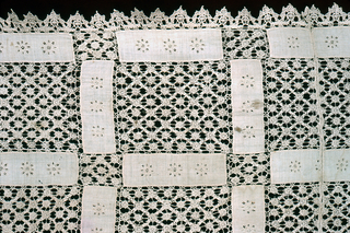 Table cover made of small plain weave rectangles ornamented with eyelets and joined with pieces of lace and filet.