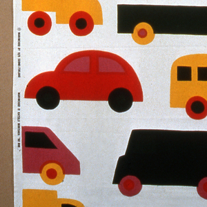 Length of printed cotton with brightly colored cars and trucks on a white ground.