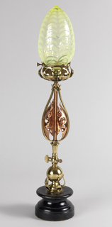 Stem with cut brass and copper leaves supporting a brass ring with striated opalescent newel post form glass globe over bulb; raised on a wood base with electrification.