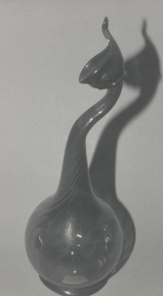 """Clear, amber-colored globular body on low circular foot.  Curved neck swirled and flattened, terminating in """"bird's head"""" mouth with narrow spout. (Rose water sprinkler)"""