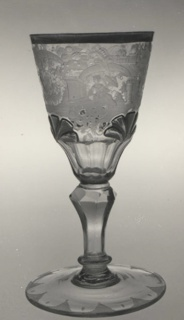 Campaniform with gilt rim and palmettes and engraved, floriated scrolls and fantastic architecture enframing a shipping scene, two seated females, and heraldic arms; panelled with cutting below. On faceted stem, ring-collared below, terminating in a round foot engraved edge with dots and serrations.