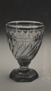 Curved sides cut with diagonal flutes and above, a row of diamonds; taperedfluted stem; 7-sided flat base; glass bluish in color, heavy; cutting clumsy.