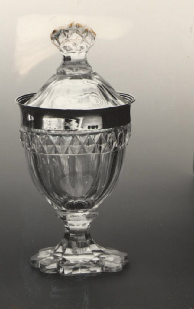 Flattened urn-shaped body on tall faceted flaring foot with scalloped edge;sides of body fluted, a band of diamonds above, above that a band of silverwith slightly everted lip; high domed cover with faceted sides and finial cut with diamonds, notch cut out of rim for spoon.