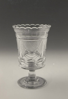 Tall straight sides slightly flared at scalloped top rim, flat bottom, tall spool stem on flat circular base; sides cut with large swags with small diamonds above and a row of losenges below, under rim has a row of facets with blazes on each side.