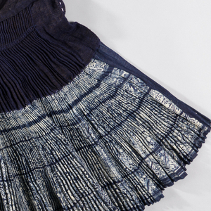 "Indigo resist-dyed skirt made from hand-spun yarns. The waistband and upper pleated band are solid blue while the lower pleated band of the skirt is patterned with five rings of hand-drawn designs including sawtooth and ""Greek key"" type patterns. Upper pleated band has decorative stitches to hold pleating in place."