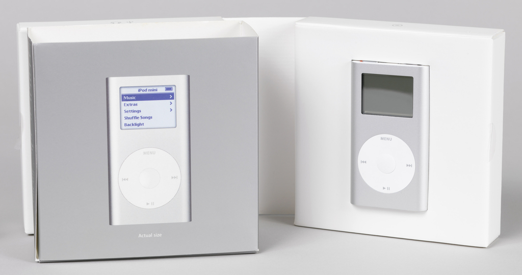 "Flat silver rectangular form with curved sides; white panels on top and bottom with switch and ports for cord and earphones; on front, clear rectangular digital readout screen above circular white control with the word ""Menu,"" and arrow symbols for 'back,' 'forward,' 'pause.'"