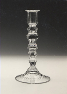 Tall shaft with series of faceted knops; faceted nozzle with cut and shape everted rim; domed base spreading to flat circular rim, cut with facets at top and with circular row of printies on underside, notched around bottom outer rim; pontil mark; glass greenish, light, bubbly.