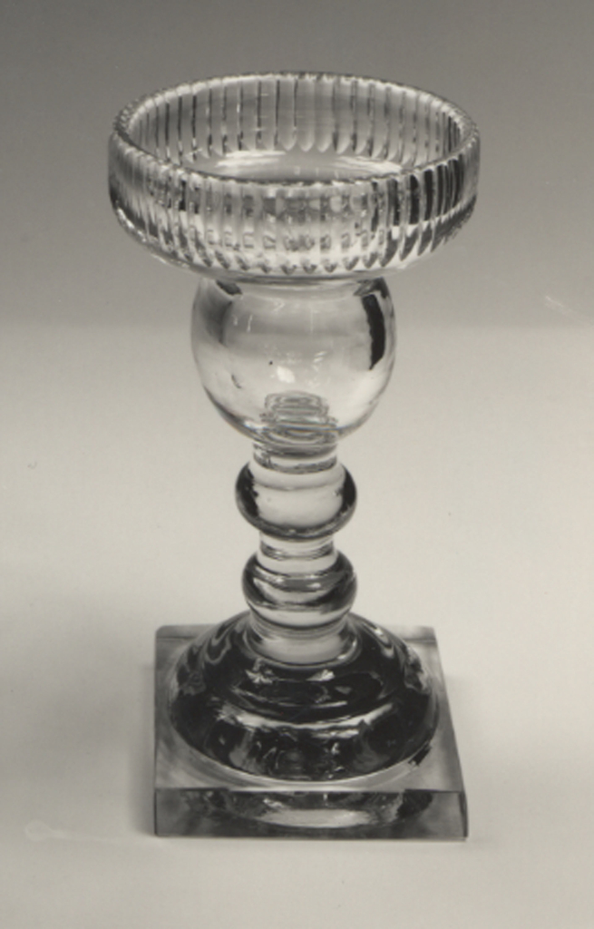 Tall double-knopped shaft on domed, stepped base with thick square foot, bulbous nozzle, wide drip pan with up-turned edge cut with vertical flutes;removable brass drip pans; glass clear and heavy; shaft leans to one side.