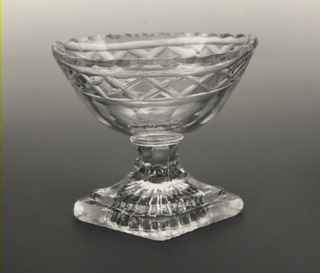 Oval bowl on tall spreading fluted stem, diamond-shaped base with molded star fluting on bottom; sides of bowl cut with scalloped edge, flat diamond band and a row of printies; glass greenish, bubbly.