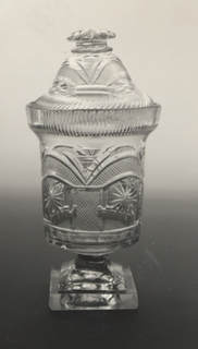 Straight sided jar with projecting rim and domed lid Jar has 4 arch and pillar sections of fine diamonds which enclose 4 cut stars. Rim has fine diagonal blazes, 3 arches of fine diamonds, mushroom finial square-sided stem, square pedestal base.