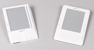 Canted rectangular form of white plastic with large rectangular flat screen set above keyboard occupying slanted lower quarter of face; small rectangular keys set at angle; large rectangular function keys flanking screen; small scroll wheel above right side of keyboard; input jacks and volume control on bottom; grey plastic panel on back.