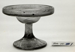 Inverted bell shape, shallow, with upright lip.  On high stem and ireegularly circular foot incised with straight, branching lines.
