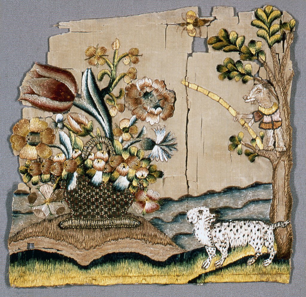 Fragment show a basket of flowers resting on a small mound.  Background has wavy blue lines suggesting water. Foreground has grass and a tree on the right. A black and white spotted dog stands near the tree while a small creature or animal in a tunic stands on a tree branch.