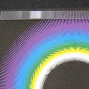 """In top third of poster, a multicolored arc like a rainbow in white, yellow, green, blue and purple. Below it, similar but larger arc in same colors. Across bottom, text in white reads: """"'83/ the 10th/ tokyo/ international lighting design competition/ Theme: Lighting as Communication."""" Black background."""