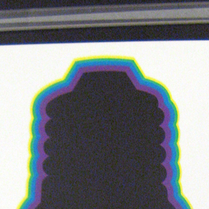 White poster with black border. In center, silhouette of a lightbulb in black. Edges of lightbulb have aura in concentric layers of purple, blue, green and yellow. At bottom, on black border in white, Japanese text.