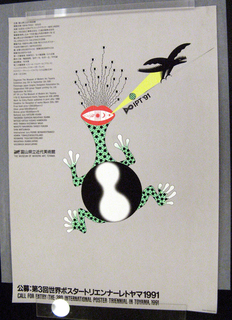 """Grey poster with text in black down left side and also across bottom from left to right. In center, a green and black creature with four legs, large red mouth containing five symbols, and multiple eyes on black stalks atop its head. In top right, black dragon-like creature flying away from the first creature, carrying a white spear and training a yellow beam down to creature's mouth. In top left corner down side, Japanese text in black. Below, English text in black outlining competition prizes and submission guideline. Across bottom of poster, Japanese text in black followed by English text in black reading: """"CALL FOR ENTRY: THE 3RD INTERNATIONAL POSTER TRIENNIAL IN TOYAMA, 1991"""""""
