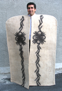 Cloak with broadly rounded shoulders in natural wool white, with a pattern band down each side front in black. Center front opening.