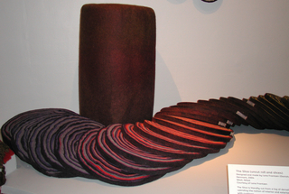 Cushion of colored wools felted into a log form and then sliced, giving the effect of the rings of a tree. In shades of brown, purple, green and red, varying in composition from predominantly purple to predominantly red.