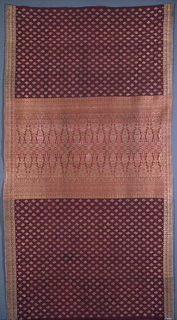"""Brocaded sarong (kain songket) with a maroon silk warp and purple silk weft, brocaded with an all-over repeating leaf pattern in gold thread. Geometric borders brocaded in gold and a wide center band heavily brocaded in gold in the stylized """"lawi ayam"""" or 'cockerel's tail feathers' motif."""