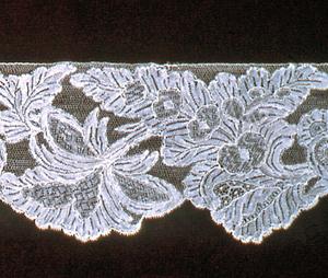 Band of Point de Venise à Réseau in a design of floral clusters balanced by foliated forms in a dense, allover pattern. Fond: bride tortillée. Modes: portes, enchainettes.