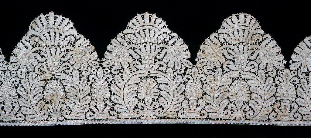 L-shaped part of a lace border. Scalloped in a floral motif with large blossoms creating the scalloped edge of the band.
