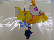 Two pieces of clear plastic stapled one atop the other. A cartoon-style yellow submarine on lower sheet; a white haired man in naval uniform (Sgt. Pepper) squatting beneath a blue anchor on superimposed sheet.