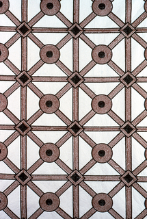 White synthetic leather embroidered in a grid pattern: a diamond grid superimposed on a square grid, whit whites on diamonds at the crossings. Light brown outlined with dull green.