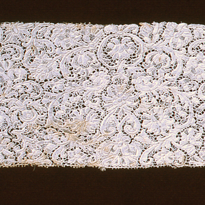 Border of small scale floral and foliated forms in intricate repeat designs. Patterns connected by brides picotées and outlined by cordonnet.